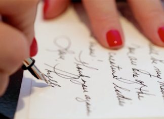 A photo of a woman signing a letter