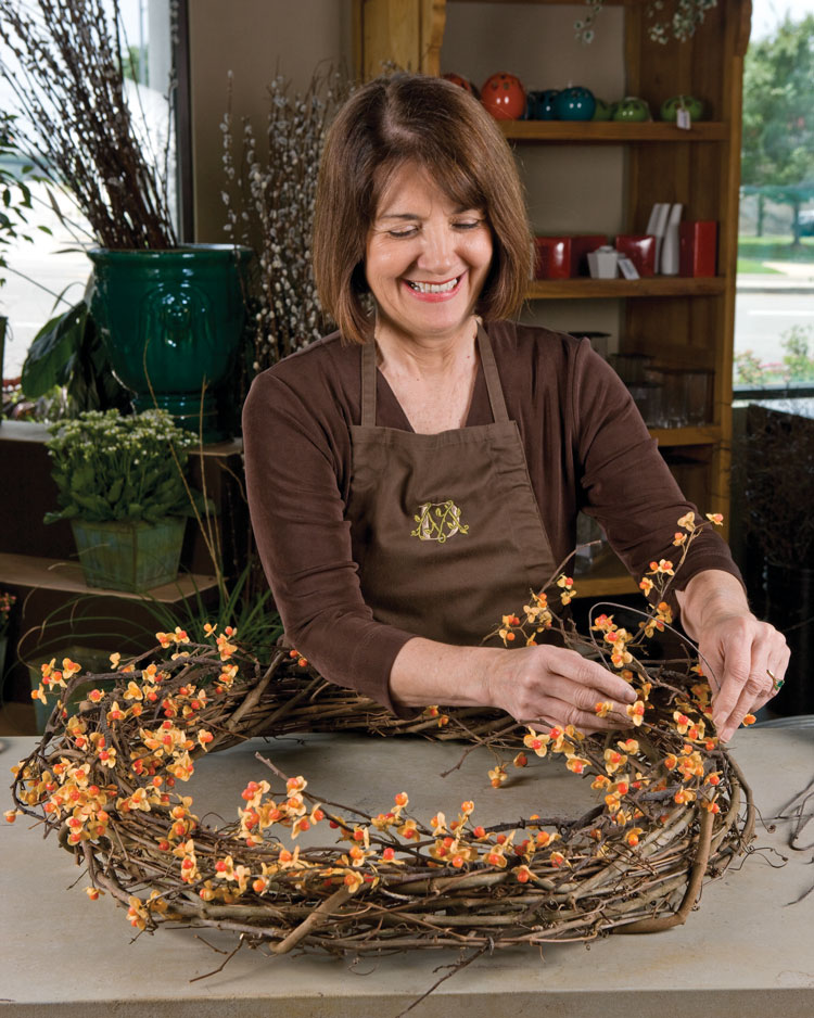 A step-by-step photo of a grapevine wreath with sunflowers and fall flowers