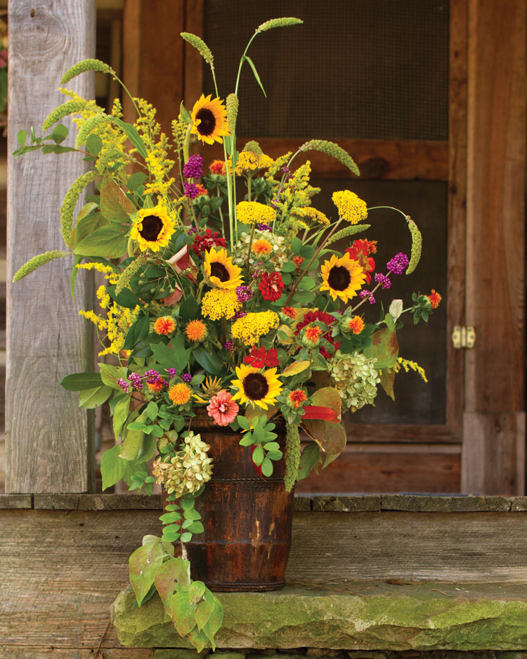 A photo of a fall flower arrangement with sunflowers