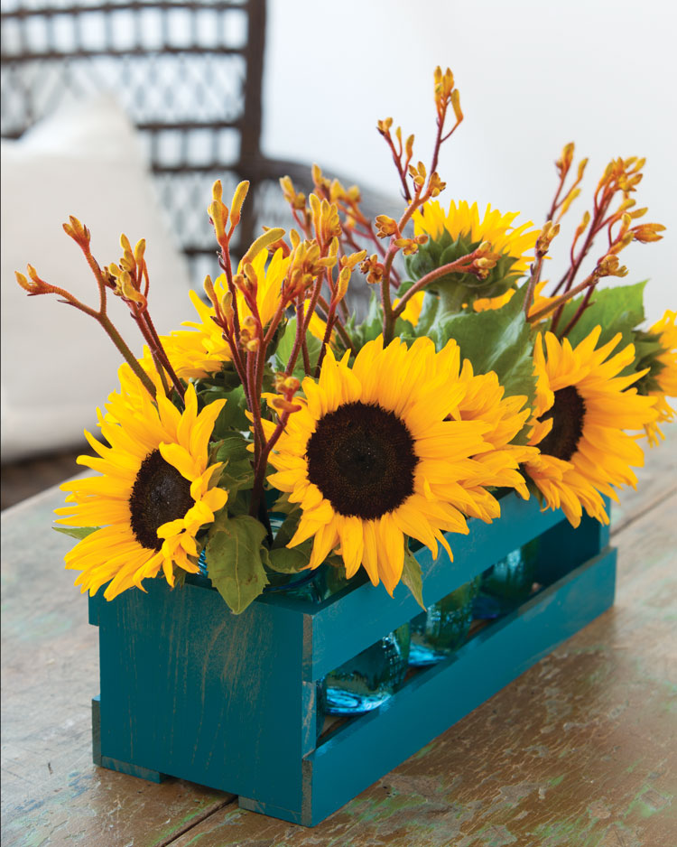 A photo of sunflowers in mason jars and a wooden crate