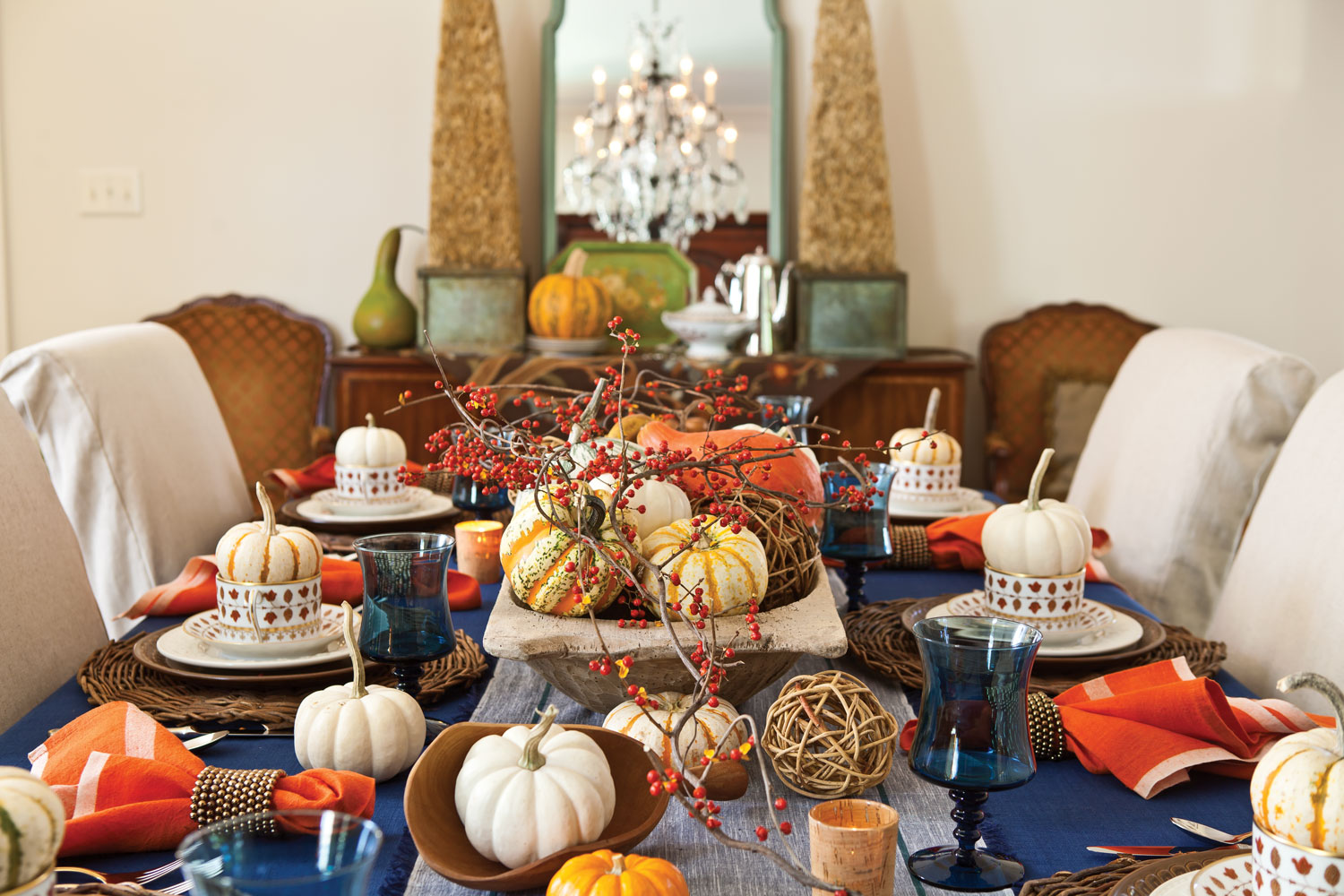 A picture of a table display with pumpkins and other fall elements