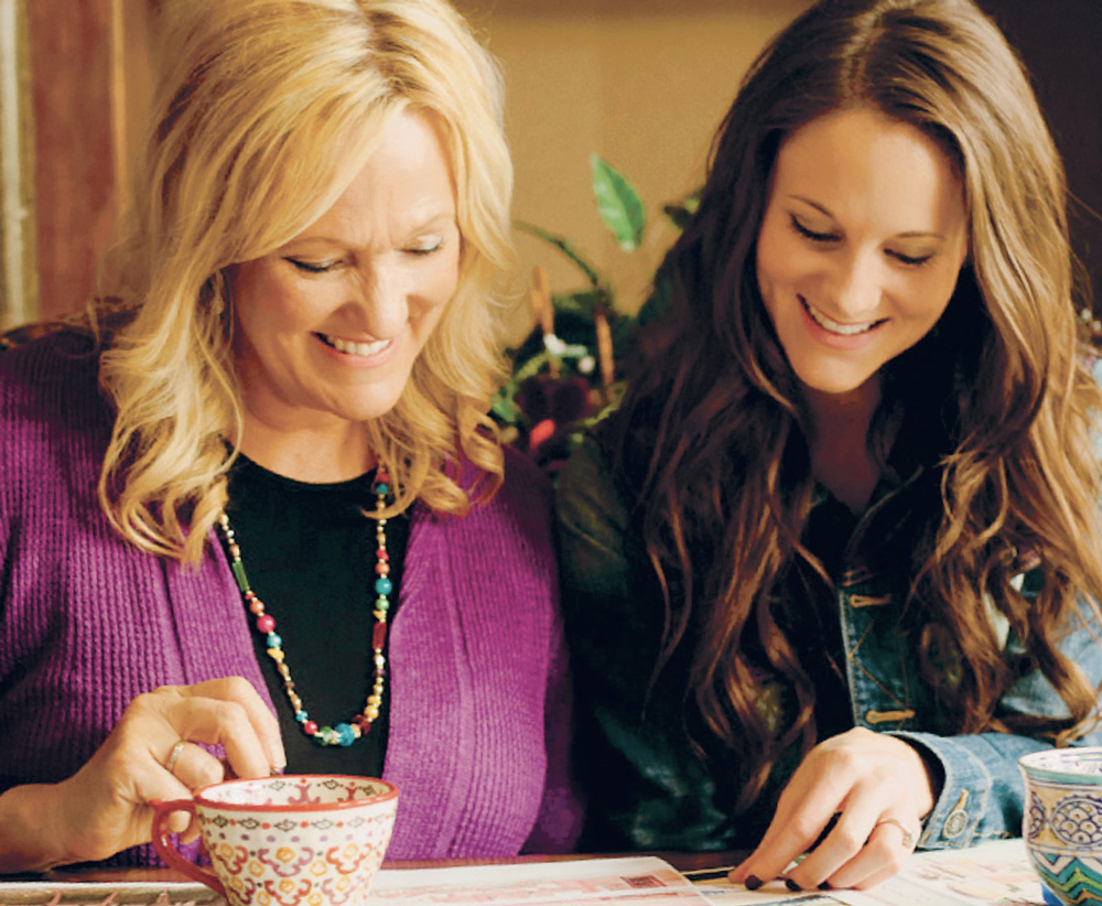 A picture of best-selling author Karen Kingsbury and daughter Kelsey Kupecky as they work on their greeting card and gift line, Possibilities