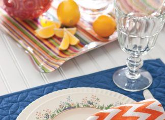 A photo of a an orange-and-white chevron napkin and the Lenox Rutledge china pattern.