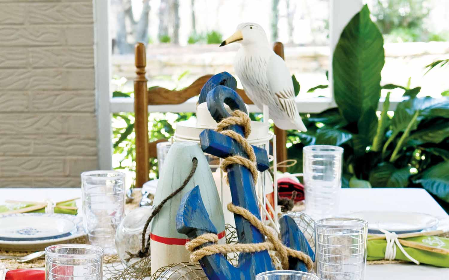 A picture of a tablescape with a nautical theme that includes an anchor as a centerpiece.