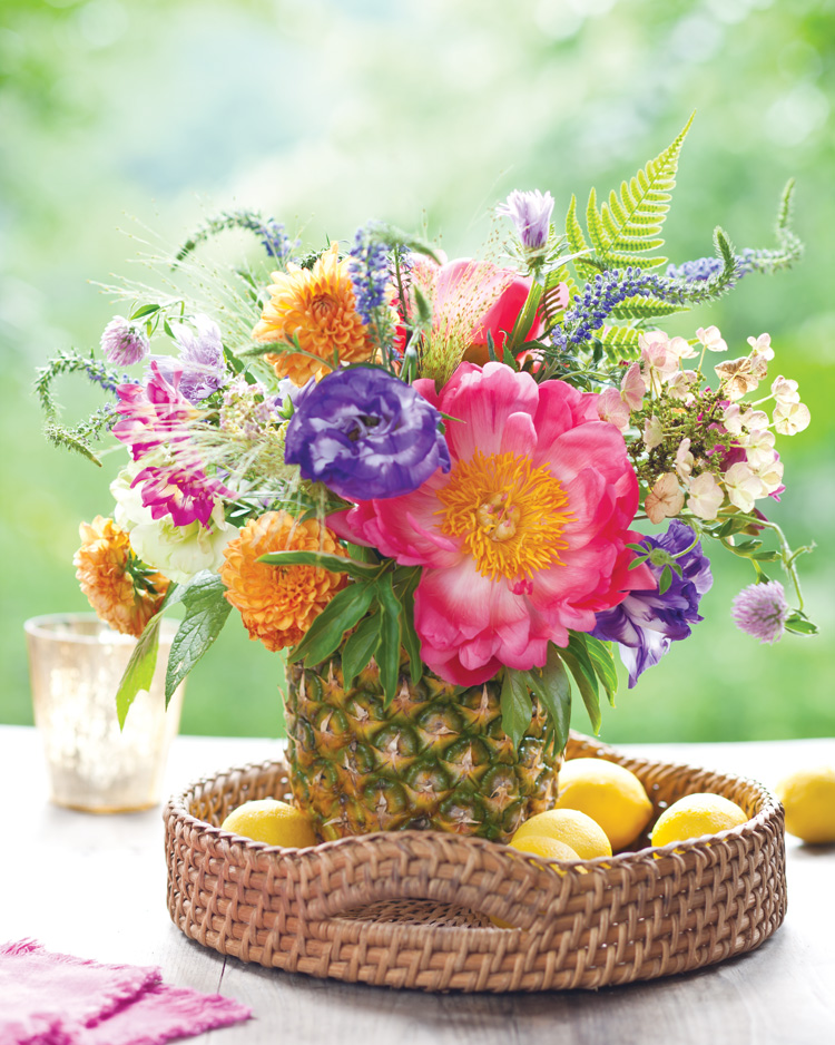 A picture of a summer floral arrangement in a fruit-turned-vase